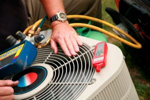 air conditioner with tools on top and technician's hands working on it