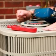 outside unit of an air conditioner with tools and hands resting on top